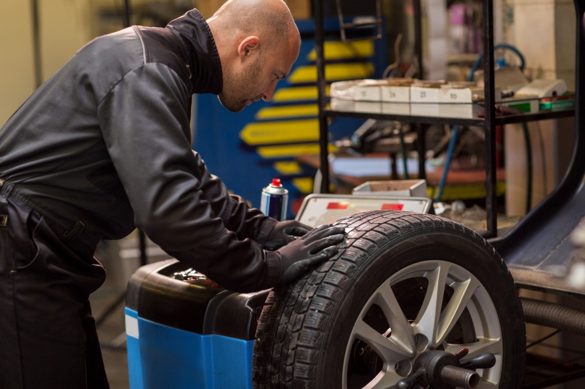 mechanic balancing a tire in the auto shop